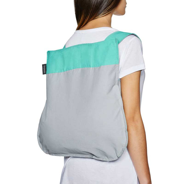 Notabag Mint & Grey 2 in one tote and backpack  shown on a lady's back