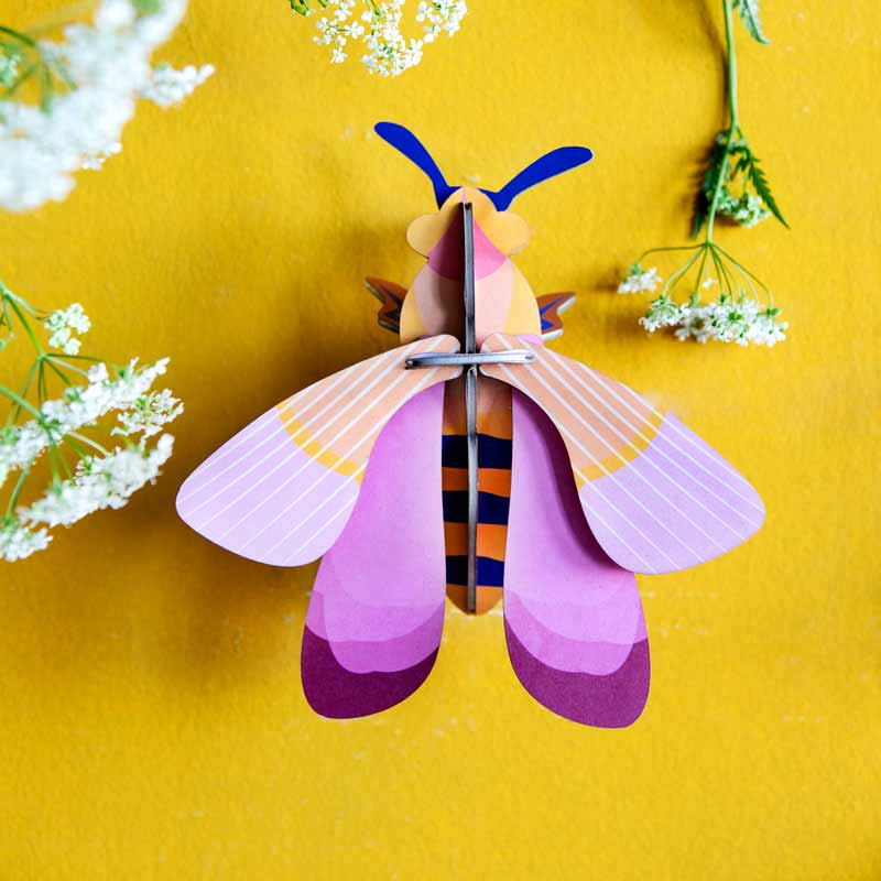 Studio Roof Pink Bee Wall Decoration shown on yellow wall