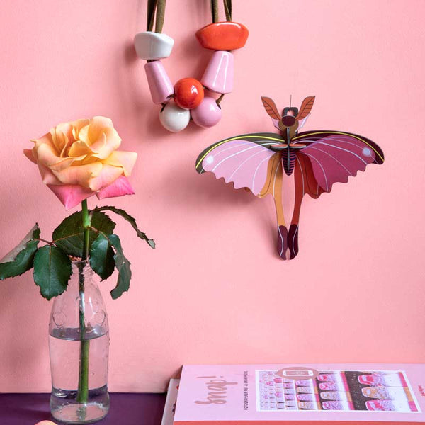 Studio Roof Pink Commet Butterfly Wall Decoration shown on pink wall