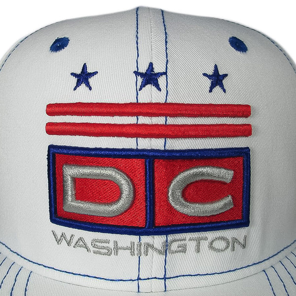 Closeup of white snapback with blue stitching. Washington DC logo embroidered on front