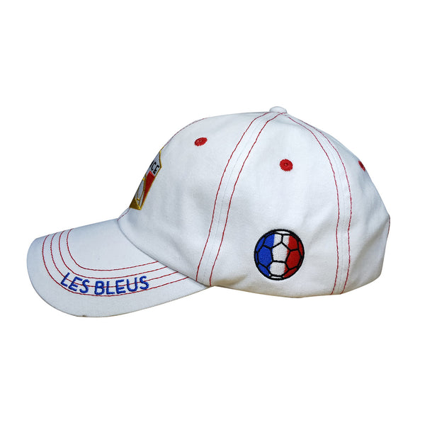 Side view of white cap, red stitching, embroidered France insignia on front, bill reads Les Bleus, football in colors of French flag on side