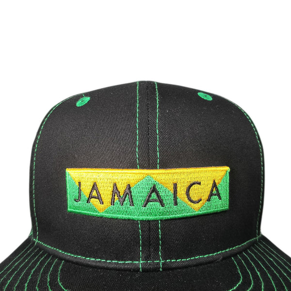 Closeup of black snapback with green stitching, Jamaica design embroidered on front
