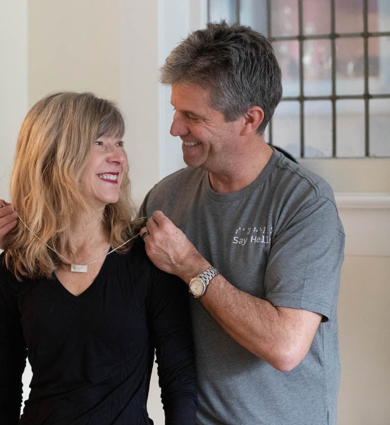 Norm wears the heather grey short sleeved cotton t-shirt.  He is placing a say hello sterling silver necklace around the neck of his wife, Violet.