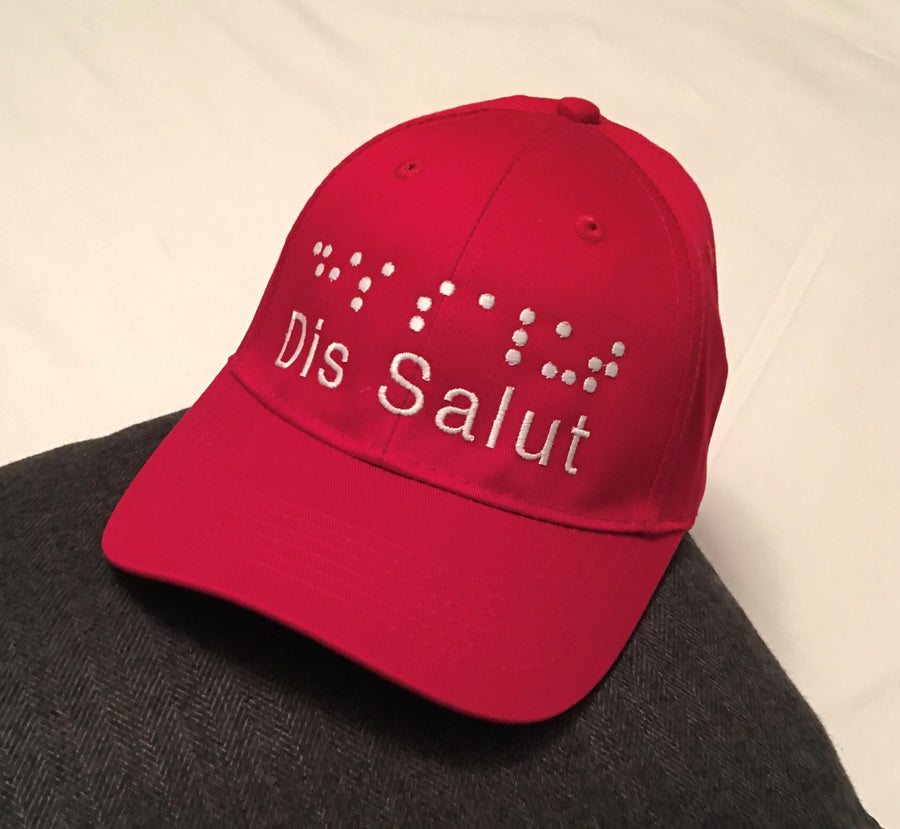 A youth red cap with the white raised embroidery logo dis salut in letters and braille above the letters.
