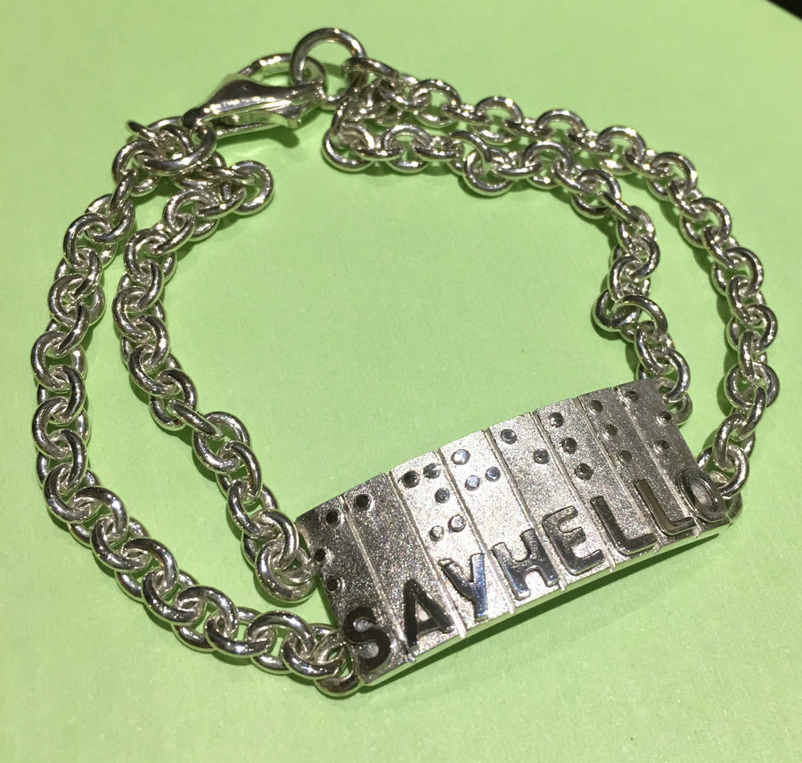 Sterling Silver Bracelet.Individually hand crafted in Canada.Rectangular tag with raised letters and braille saying Say Hello.
