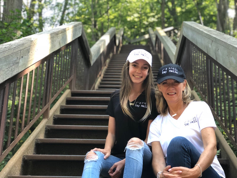 One woman wears a white with black logo baseball cap.  The other woman wears a black with white loge baseball cap.Logo in raised embroidery saying say hello in braille and letters.