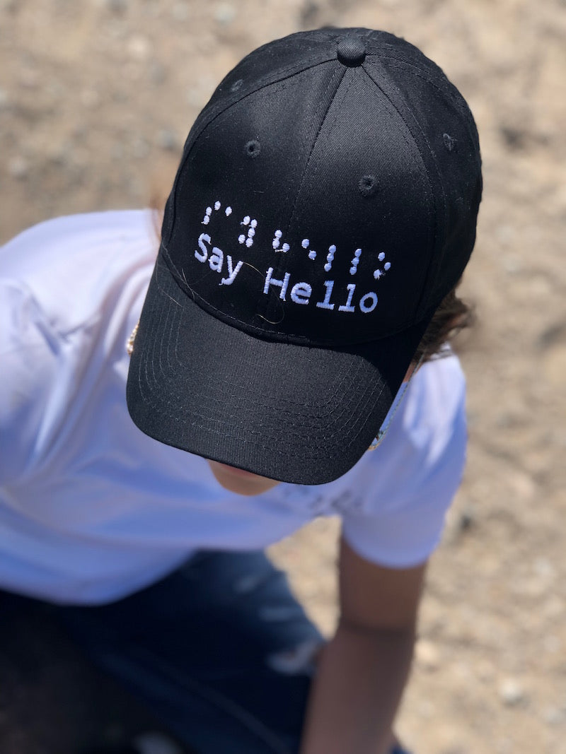 Black baseball cap with white raised embroidery saying say hello in braille and letters.