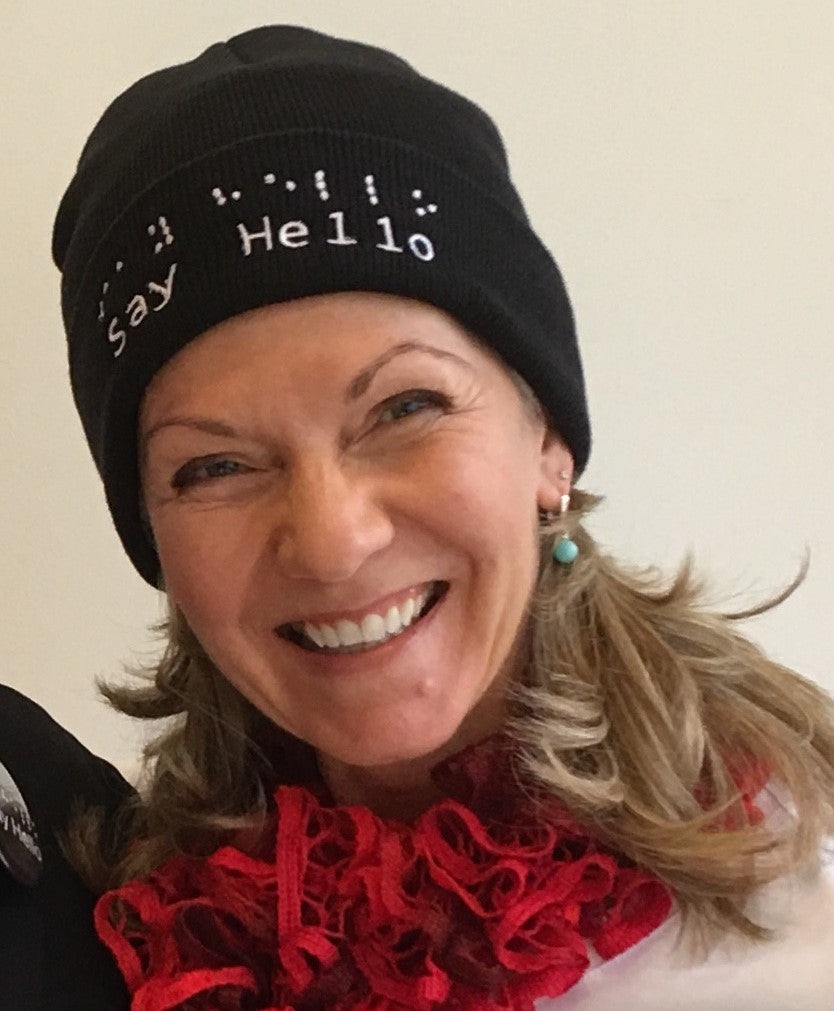 Denise, long blonde hair and big smile, wears a black toque with white embroidery say hello logo in words and braille.