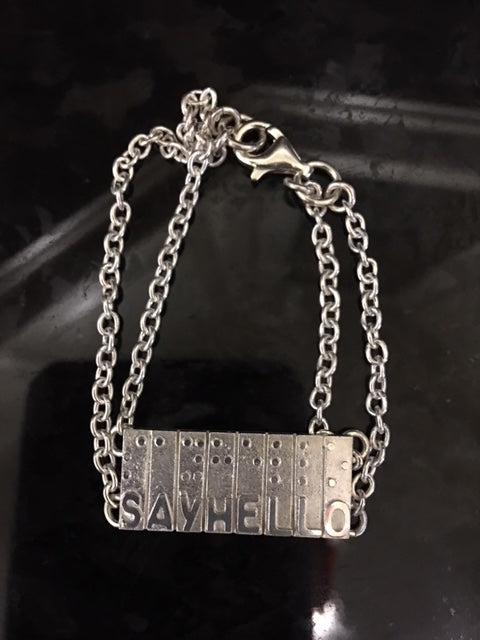Sterling Silver bracelet.Individually hand crafted in Canada.Rectangular tag with raised braille and letters saying Say Hello.