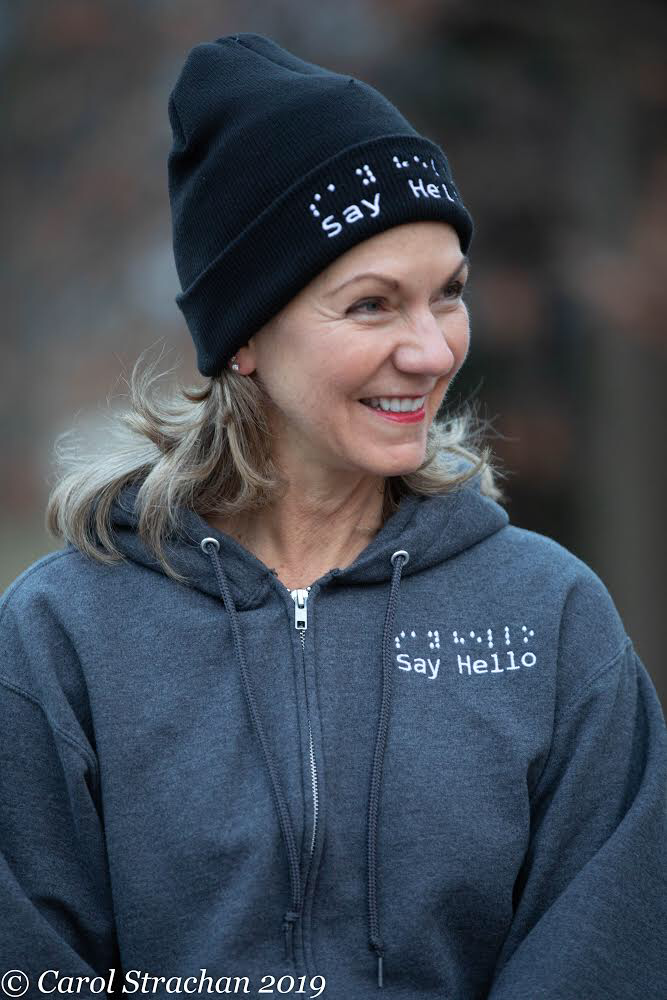 Denise wears a heather grey full zip hoodie with the raised embroidered say hello logo in white.