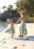 Mom and daughter spinning around in matching floral summer dresses