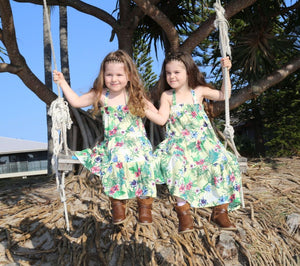 2 sisters on a swing in matching summer printed dress