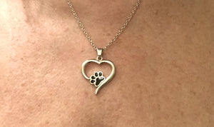 Heart shaped pendant with paw print around a lady's neck