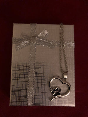 Heart shaped pendant with paw print on top of silver box