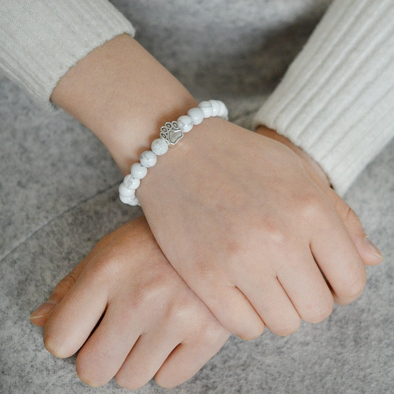 ladies hands crossed with white chakra bracelet on one wrist