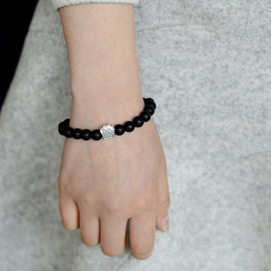lady's hand hanging by her side wearing a black chakra bracelet