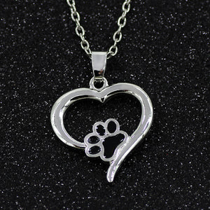 Heart shaped pendant with paw print on black background