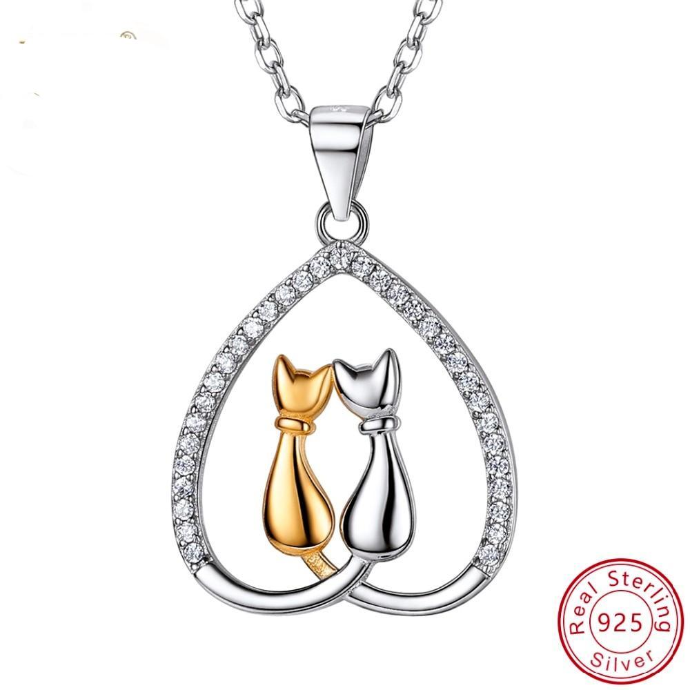 pendant with 2 cats one gold and one silver. Their tails are encrusted with cubic zirconia and form an inverted heart