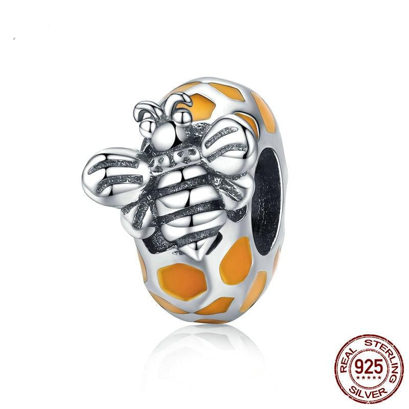silver bracelet charm featuring a little silver bee on silver and yellow enamel honeycomb design