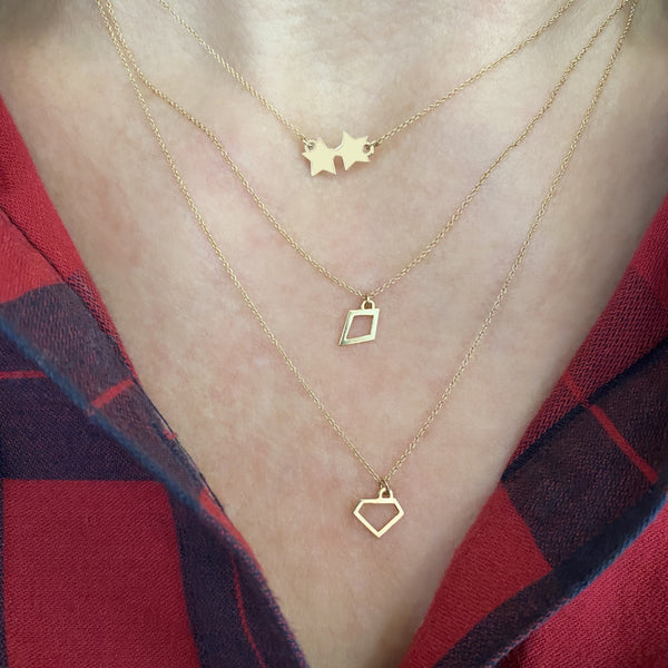 14k gold layering necklaces, including a double star necklace, open kite charm necklace, and open gem-shaped charm necklace on a woman's neck. she is wearing a red and navy blue plaid shirt.