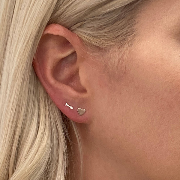 close up view of a woman's ear and some of her blonde hair. she's wearing a sterling silver arrow stud earring and a sterling silver heart stud earring