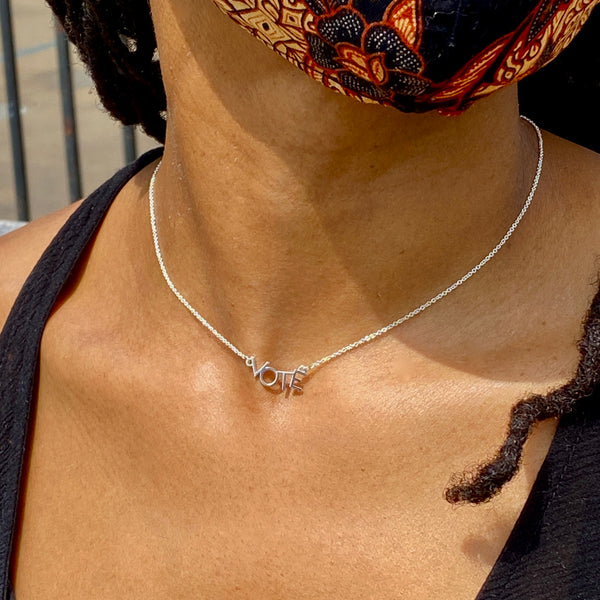 "close up of a woman's neck and she's wearing a short sterling silver necklace that says ""VOTE""."