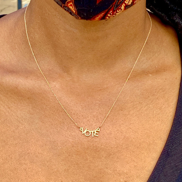 "Close up shot of a woman's neck with a gold necklace that says ""VOTE"" at the front."