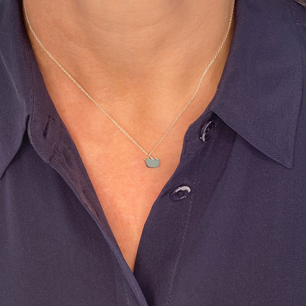 sterling silver crown charm necklace, shown on a partial view of a woman's neck and chest and she is wearing a navy blue collared blouse