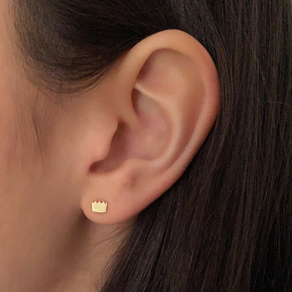 14k yellow gold crown stud earring on a woman's ear