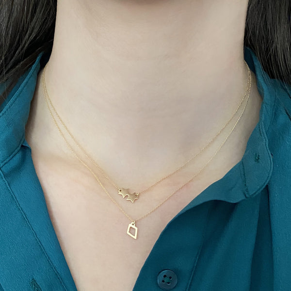 14k gold double star necklace and 14k gold kite charm necklace on a woman's neck