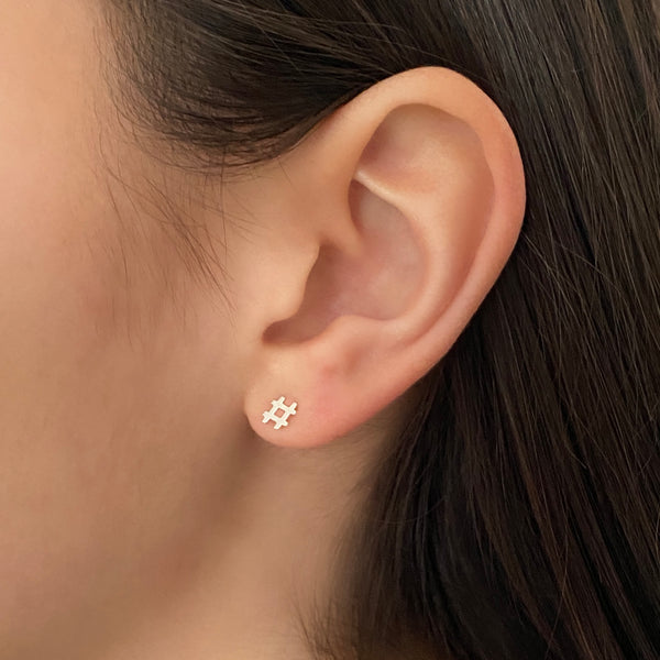 close up shot of a woman's ear and she's wearing a sterling silver hashtag stud earring
