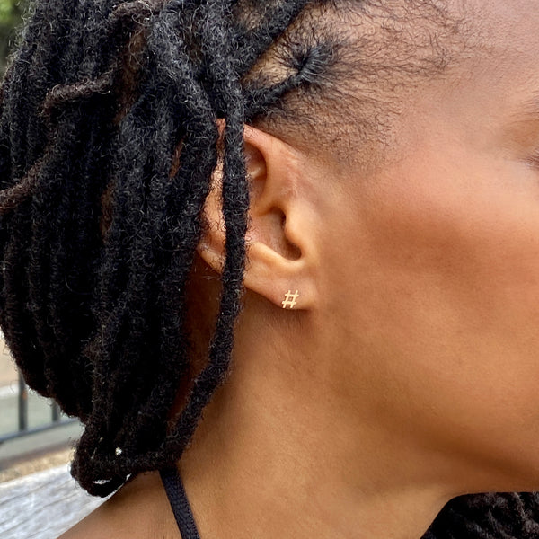 partial side view of a woman's head and you can see some of her hair in long twists, her ear, and most of her cheek. She's wearing a yellow gold hashtag stud earring.