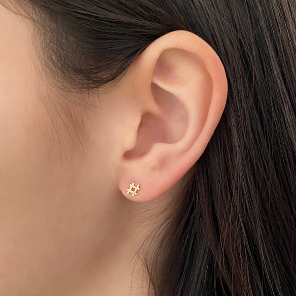 close up side view of a woman's ear and she's wearing a yellow gold hashtag stud earring