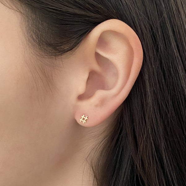 14k gold hashtag stud earring on a woman's ear