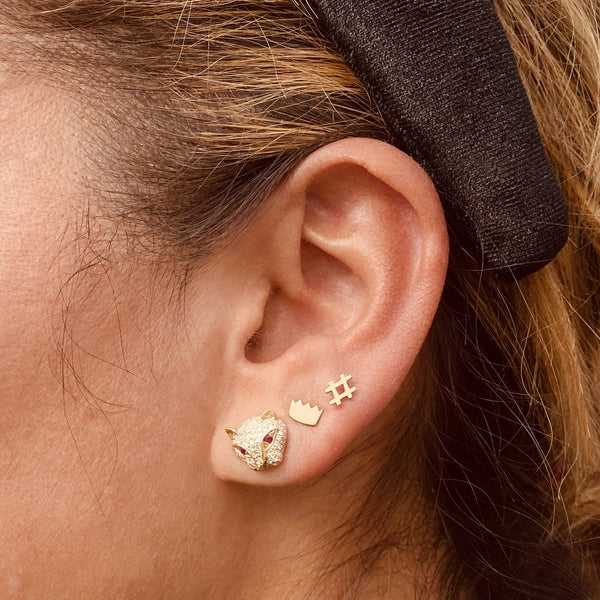 Tiger stud earring and 14k gold crown stud earring and 14k gold hashtag stud earring on a woman's ear