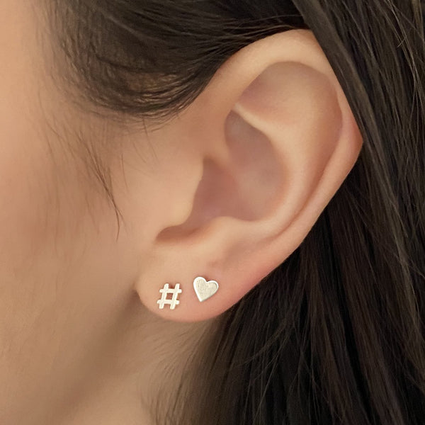 sterling silver hashtag stud earring and sterling silver heart stud earring on woman's ear.