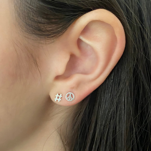 sterling silver hashtag stud earring and sterling silver peace symbol stud earring on a woman's ear