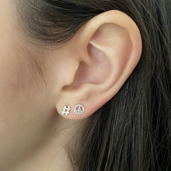 sterling silver hashtag stud earring and sterling silver peace symbol stud earring on woman's ear