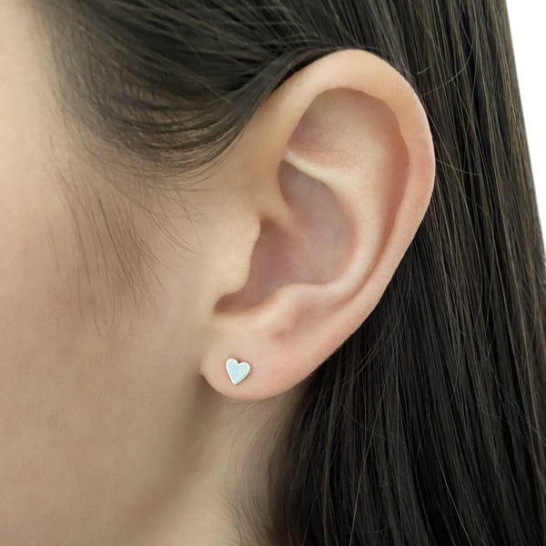 sterling silver heart stud earring on woman's ear