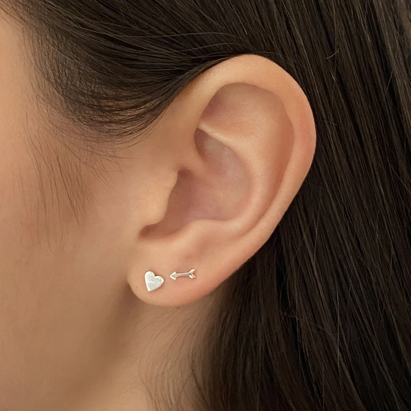 close up view of a woman's ear and some of her brown hair. she's wearing a sterling silver arrow stud earring and a sterling silver heart stud earring