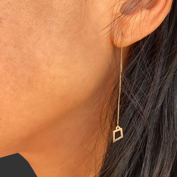 close up view of a woman's ear and some of her dark brown hair. she's wearing a 14k yellow gold kite threader earring