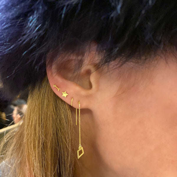close up view of a woman's ear, part of a furry blue hat, and some of her blonde hair tucked behind her ear is visible. She's wearing 3 earrings: a 14k yellow gold kite threader earring threaded through her first and second ear piercings, a 14k yellow gold star stud earring above that, and a 14k yellow gold arrow stud earring in the fourth piercing.