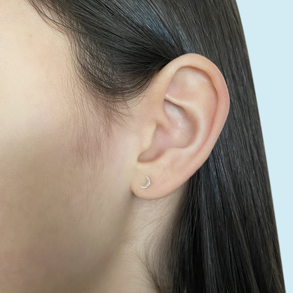sterling silver crescent moon stud earring on a woman's ear