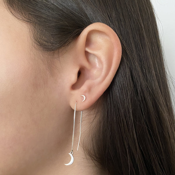 sterling silver crescent moon threader earring and sterling silver crescent moon stud earring on a woman's ear