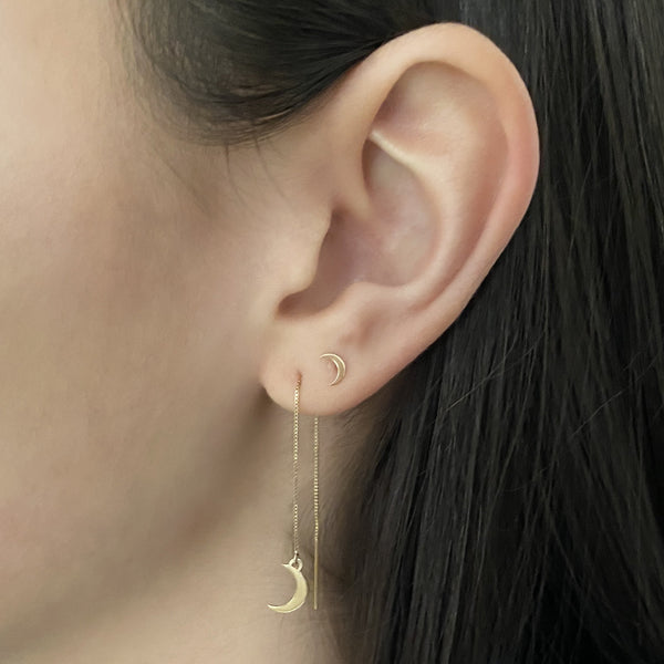 14k gold crescent moon threader earring and 14k gold crescent moon stud earring on a woman's ear