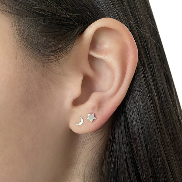 sterling silver crescent moon stud earring and sterling silver star stud earring on woman's ear