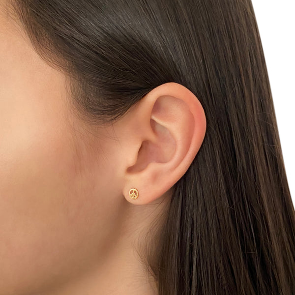 14k gold peace symbol stud earring on a woman's ear