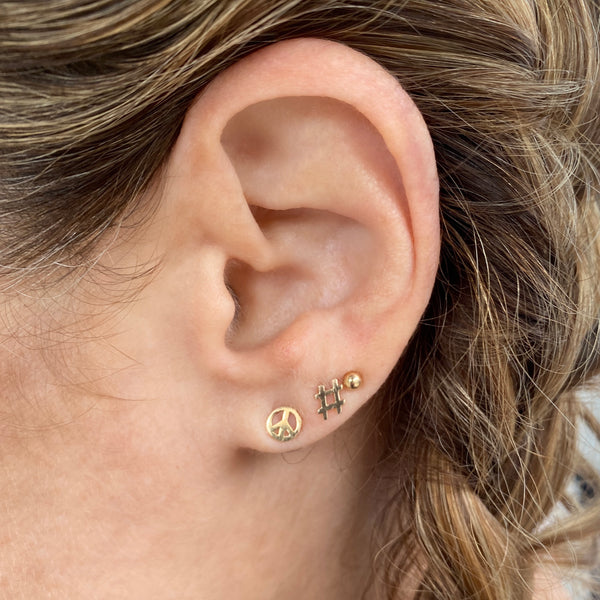 Close up of a woman's ear and she's wearing three earrings. She's wearing a 14k gold peace symbol stud earring in the first hole, a 14k yellow gold hashtag earring in her second hole, and a simple stud earring in her third hole. Some of her light brown hair is visible and it's in a braid.