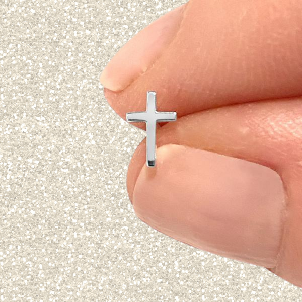 sterling silver cross stud earring held between a peron's thumb and index finger