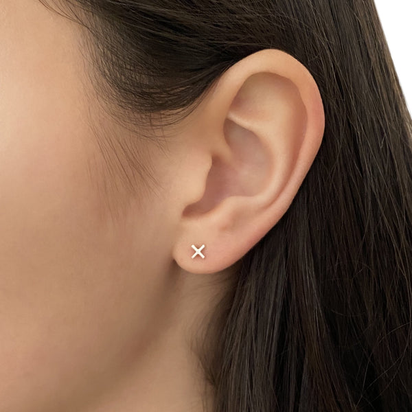 sterling silver Plus symbol stud earring on a woman's ear